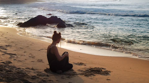 exciting lady in black tracksuit sits on ocean sand beach Footage