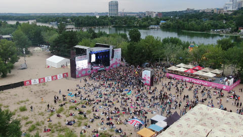 Festival with a stage on the beach, artists are performing on stage Live Action