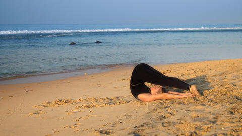 exciting barefoot lady lies on yellow sand in yoga position Footage