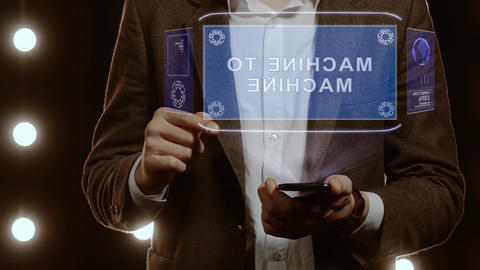 Businessman uses hologram with text Machine to machine Live Action