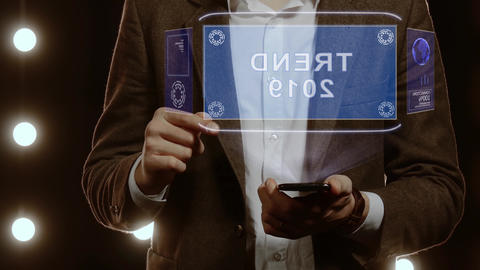 Businessman uses hologram with text Trend 2019 Live Action
