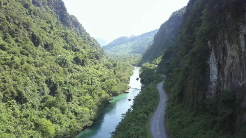 road and river meander between steep lush forestry banks Footage