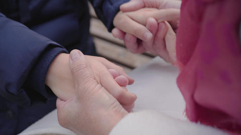 Close-up of female mature Caucasian hands holding hands of a young girl. Unity Live Action