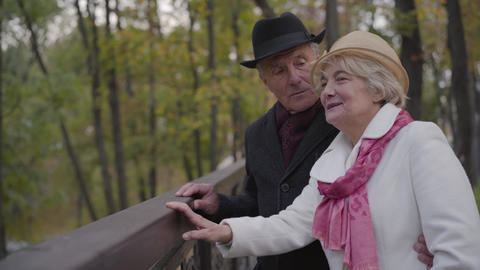 Side view of a mature Caucasian couple standing next to the handrails and Footage