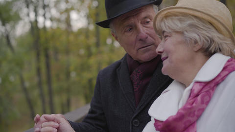 Close-up of a mature Caucasian couple standing next to the handrails and talking Footage