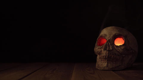 Man place on wood table human old skull with luminous eyes and coming out of Footage