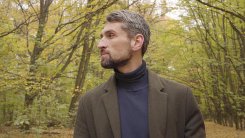 Close-up of a confident Caucasian man with grey hair and brown eyes turning to Footage