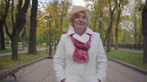 Close-up of Caucasian woman in elegant beige cloche hat and white coat strolling Footage
