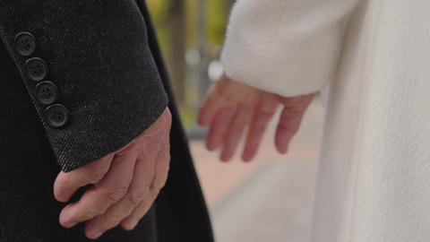 Close-up of mature Caucasian hands joining. Male hand in black coat and female Live Action