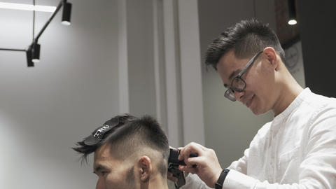 Asian male hairdresser cuts clients hair Live Action