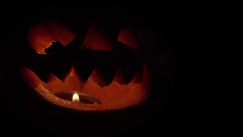 Isolated smiling jack-o-lantern with burning candle and smoke inside Footage