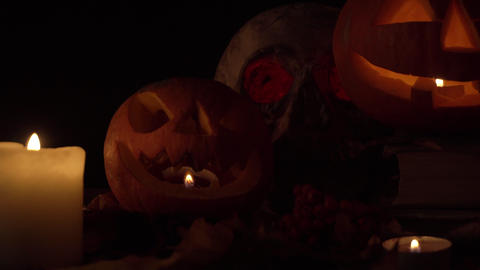 Two pumpkins with carved faces and a skull in candlelight, loop video Live Action
