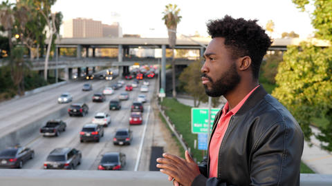 African-American man walks across a bridge over a freeway Live Action
