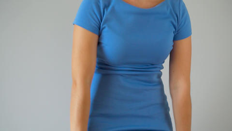 Woman in slimming panties wears a blue dress on top and checks the result Live Action