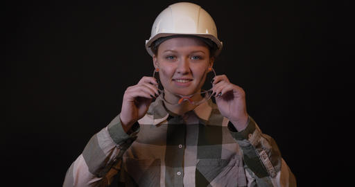 Young female engineer puts on protective glasses Footage