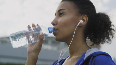 African American teenager girl drinking cold water after running in the park in Live Action