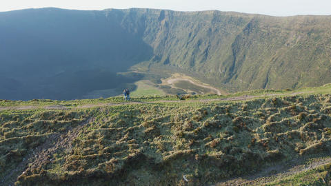 Two people stay at the edge of caldera. Aerial of Faial volcano, Azores Live Action