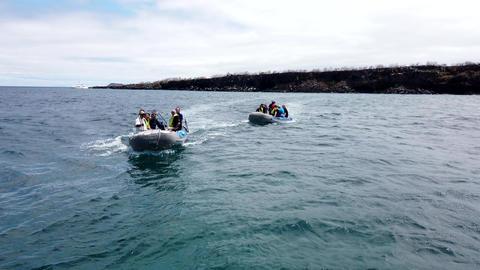 Galapagos, Ecuador - 2019-06-20 - Two island landing boats approach tour boat Live Action