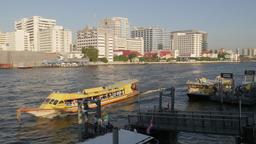 Ferry on Chao Praya river with Sirraj hospital,Bangkok,Thailand Footage