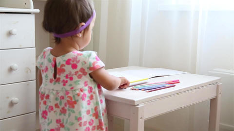 Little girl in nursery in flower dress learning to draw with brown pencil HD Footage