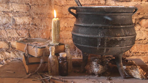 diabolic witch night spell with candles and pot with fire between cobwebs and ancient earth Live Action