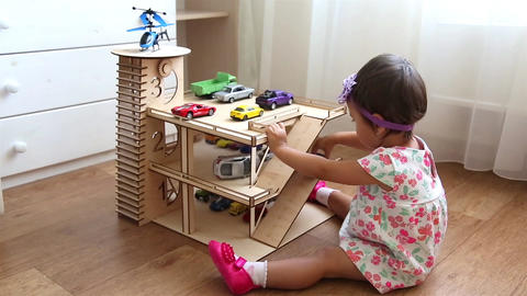 Small child playing in kindergarten in toy garage with small cars and helicopter Live Action