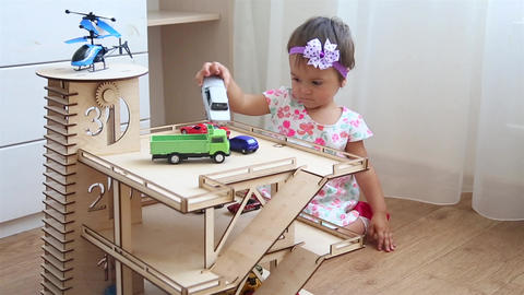 Girl in dress playing in kindergarten in toy garage with small cars and Footage