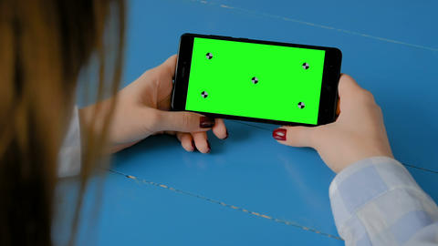 Woman looking at black smartphone with empty green screen - chroma key concept Footage