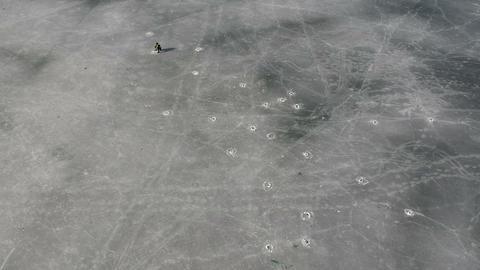Lonely fisherman and many ice hole on spring lake ice, aerial view Live Action