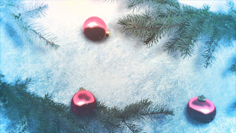 Animated close up red balls and Christmas green tree branches on shiny ice background Animation