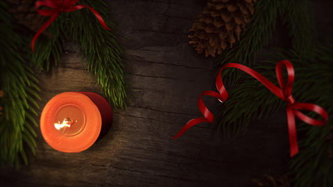 Animated close up Christmas candle and green tree branches on wood background Animation