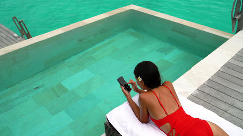 Lady using phone relaxing in the sun by pool on beach in on vacation Footage