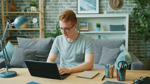 Young male freelancer working at home using laptop typing and smiling Footage