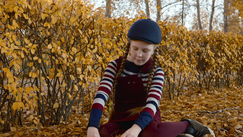 Cute teenager girl with red haired braids throwing yellow leaves in autumn park Footage