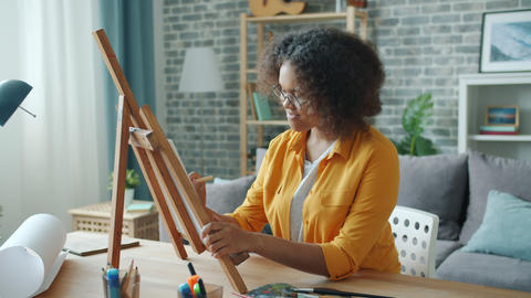 Slow motion of young artist African American girl painting at home at desk Footage