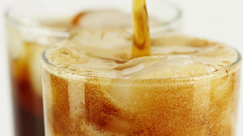Pouring cola soft drink with ice cubes into a glass, close-up slow motion shot Footage
