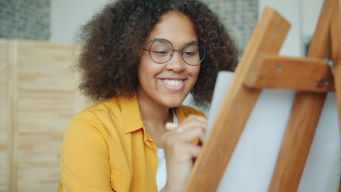 Happy African American teenager drawing picture at home smiling enjoying hobby Live Action