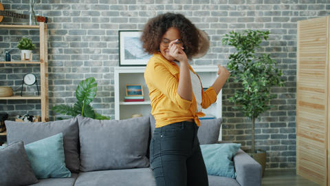 African American student is having fun at home dancing looking at camera Footage