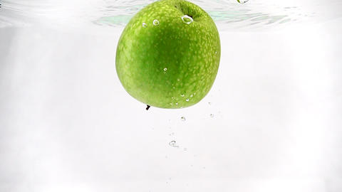 Green apple slowly immersed in water. Video in slow motion. Isolated fruit on Footage