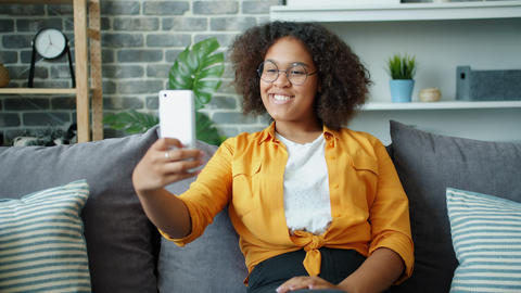 Teenage girl taking selfie with smartphone camera sitting on sofa at home Footage