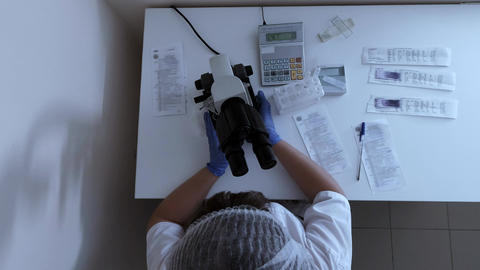 Woman lab technician comes to desktop in clinic and sit down at microscope Live Action