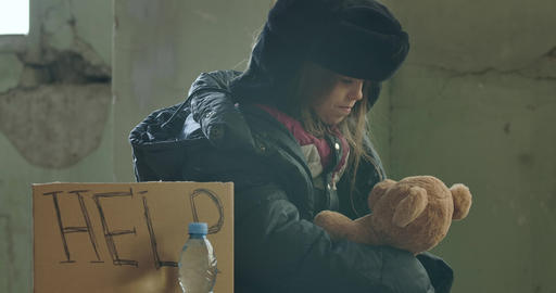Portrait of a Syrian refugee in dirty clothes sitting with Help cardboard and Live Action