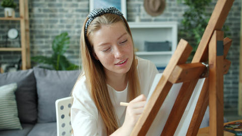 Slow motion of happy girl painting at home alone using easel, paper and pencils Live Action