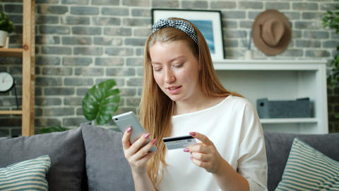 Cheerful lady shopping online paying with credit card using smartphone at home Footage