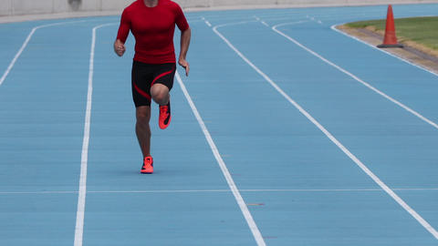 Sprinter runner athlete man sprinting training on athletics track and field Live Action
