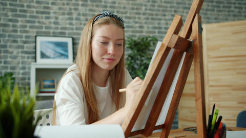 Happy young lady drawing picture at home with colored pencils sitting at easel Footage