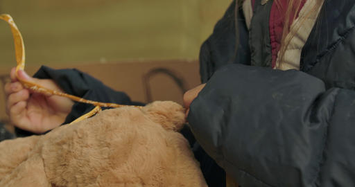 Close-up of little female hands in dirty clothes trying to tie a bow on the Live Action