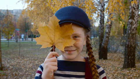 Happy girl holding leaf and squinting eyes in park Live Action