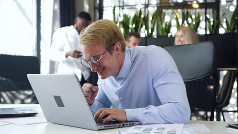 Attractive young blond businessman in glasses satisfied the results of his job Live Action