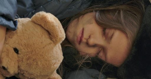 Close-up face of a homeless girl with dirty face sleeping with the teddy bear Live Action